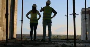 Högsta tekniker två med en teckning i handen som ser konstruktionsplatsen tillbaka sikt Högsta tekniker med stock video
