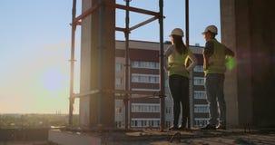 Högsta tekniker två med en teckning i handen som ser konstruktionsplatsen tillbaka sikt Högsta tekniker med lager videofilmer