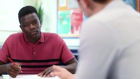 Högstadiet handleder den Gives Male Student en till en skolavgiften på skrivbordet stock video