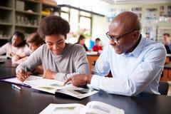 Högstadiet handleder Sitting At Desk med den manliga studenten In Biology Class arkivbild