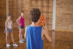 Högstadiumpojke omkring som tar ett skjutit straff, medan spela basket fotografering för bildbyråer