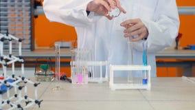 Högstadiumstudent som gör kemiprovet i labbet Händer tillfogar kemiska agens in i lilla medicinflaskan, provrör lager videofilmer