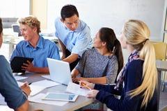 Högstadiumstudenter med lärareIn Class Using bärbara datorer arkivfoton