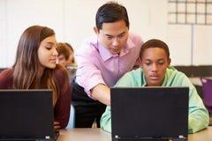 Högstadiumstudenter med lärareIn Class Using bärbara datorer fotografering för bildbyråer