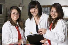 Högstadiumstudenter med professorn In Chemistry Lab fotografering för bildbyråer