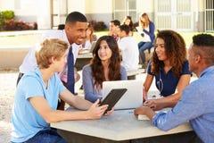 Högstadiumstudenter som arbetar på universitetsområde med läraren royaltyfri bild