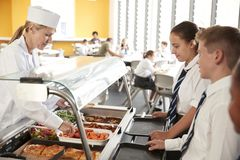 Högstadiumstudenter som bär enhetligt som tjänas som mat i kantin royaltyfria bilder