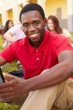 Högstadiumstudenter som utomhus studerar på universitetsområde royaltyfri fotografi