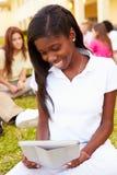 Högstadiumstudenter som utomhus studerar på universitetsområde Arkivfoto