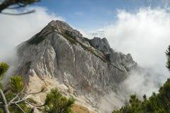 Högt berg i misten och molnen Arkivbild