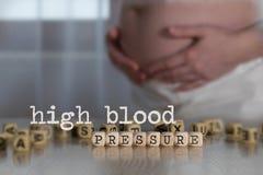 HÖGT BLODTRYCK för ord som komponeras av träbokstäver royaltyfria foton