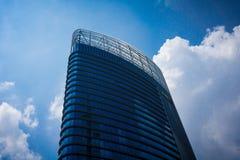 Högt byggnadskontor med blått exponeringsglas och blå himmel Arkivfoto