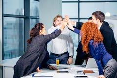 Högt-fem ungt ge sig för affärsfolk som är högt-fem på möte i regeringsställning Arkivbilder