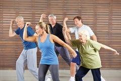 Högt folk som lär dans i idrottshallgrupp Arkivbilder