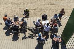 Högt folk som spelar domino på stranden, Barcelona Arkivfoto