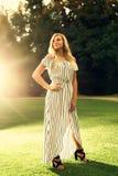 Högt foto för högstadium av blond Caucasian flickadet fria i Romperklänning royaltyfria foton