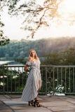 Högt foto för högstadium av blond Caucasian flickadet fria i Romperklänning arkivbilder