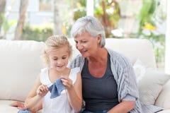 Högt handarbete med henne sondotter Arkivbilder