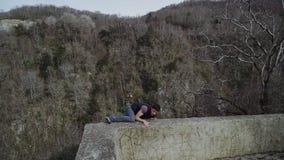 Högt i berg som en grabb klättrar på ett konkret staket, ser över och går bort arkivfilmer