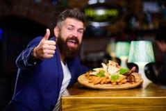 Högt kalorimellanmål Koppla av efter hård dag läcker mat Sitter den formella dräkten för affärsmannen på restaurangen Mannen mott arkivbild