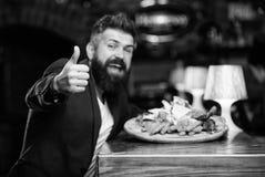 Högt kalorimellanmål Koppla av efter hård dag läcker mat Sitter den formella dräkten för affärsmannen på restaurangen Mannen mott royaltyfri foto