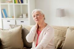 Högt kvinnalidande från hals smärtar hemma royaltyfria foton