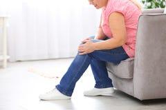 Högt kvinnalidande från knä smärtar hemma, closeupen fotografering för bildbyråer