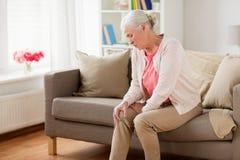Högt kvinnalidande från smärtar i ben hemma Arkivfoton