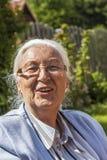 Högt kvinnasammanträde i hennes trädgård fotografering för bildbyråer