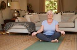Högt kvinnasammanträde i lotusblommapositionen som hemma mediterar Arkivfoton