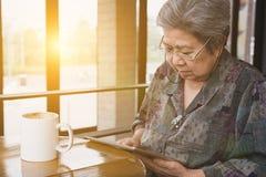 Högt kvinnasammanträde och vila i kafécoffee shop genom att använda siffran fotografering för bildbyråer