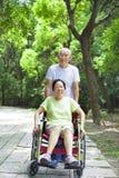 Högt kvinnasammanträde på en rullstol med hans make Arkivbild