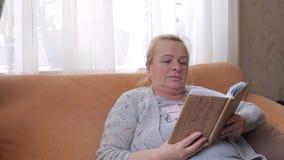Högt kvinnasammanträde på soffan och läsning en bok lager videofilmer