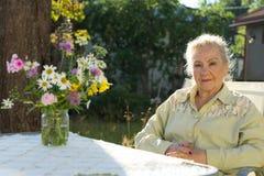 Högt kvinnasammanträde utanför på en fåtölj på trädgården royaltyfria bilder