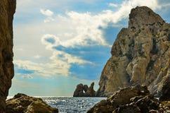 Högt och stenigt berg på den steniga kusten av havet, på en molnig himmel för bakgrund, Krim, Novy Svet Arkivfoto