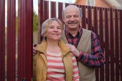 Högt paranseende vid staketet, i att le för gård arkivfoto