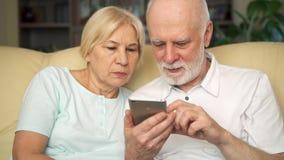 Högt parsammanträde på soffan hemma Moderna pensionärer som använder mobilen och att bläddra och att läsa nyheterna stock video