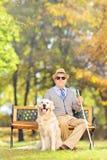 Högt sammanträde för blind man på en bänk med hans hund, i en parkera Royaltyfri Fotografi
