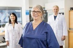 Högt sjuksköterskaSmiling While Colleagues anseende i bakgrund arkivbild