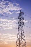 Högt spänningstorn i moln och blå himmel Fotografering för Bildbyråer