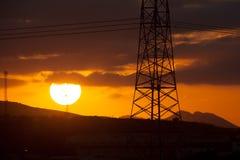 Högt spänningstorn och solnedgång Arkivfoton