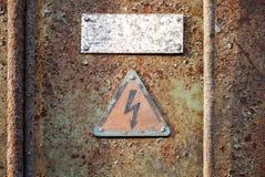 Högt spänningstriangeltecken på grungeväggen Arkivfoton