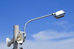 Högtalare med gatalampor på elektrisk pol Arkivfoto