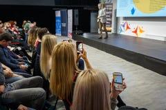 Högtalare på den affärskonferensen och presentationen Åhörare på konferenskorridoren Kvinnor antecknar på en smartphone royaltyfri fotografi
