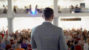 Högtalare som ger ett samtal på konferens för företags affär Åhörare på konferenskorridoren AFFÄRSHÄNDELSE En ung man in