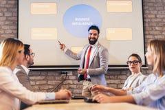 Högtalare som ger offentlig presentation genom att använda projektorn i konferensrum royaltyfri foto