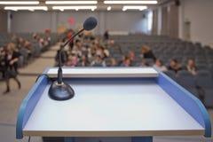 Högtalaren förbereder sig, innan den talar till åhörarna bak podiet, fokuserade mikrofonen på podiet och den suddiga tomma platse arkivbild