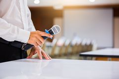 Högtalaren rymde mikrofonen i hans hand med oskarpt den konferensrum och projektorn royaltyfria foton