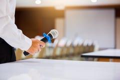 Högtalaren rymde mikrofonen i hans hand med oskarpt den konferensrum och projektorn royaltyfri bild