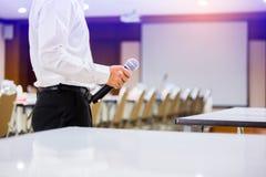 Högtalaren rymde mikrofonen i hans hand med oskarpt den konferensrum och projektorn arkivbilder